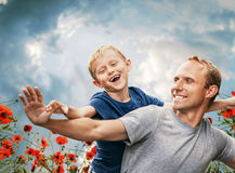 Happy smiling son and  father portrait among the poppies Royalty Free Stock Image