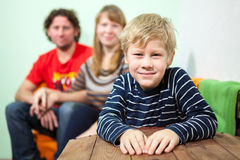 Happy smiling son sitting on foreground of his parent on sofa Stock Images