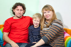 Happy smiling son sitting in between of his parent on sofa Stock Photos