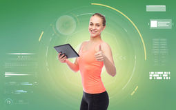 Happy smiling sportive young woman with tablet pc Royalty Free Stock Photos