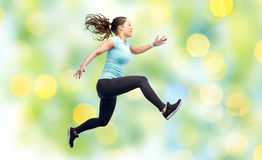 Happy smiling sporty young woman jumping in air Royalty Free Stock Photos
