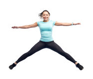Happy smiling sporty young woman jumping in air Stock Photos