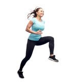 Happy smiling sporty young woman jumping in air Stock Images
