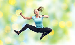 Happy smiling sporty young woman jumping in air Stock Photography