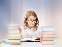 Happy smiling student girl reading book. Education, people, children and school concept - happy smiling student girl reading book over rose quartz and serenity Royalty Free Stock Photography