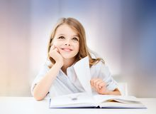 Happy smiling student girl reading book. Education, people, children and school concept - happy smiling student girl reading book over rose quartz and serenity Stock Photography