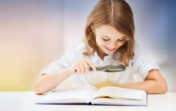 Happy smiling student girl reading book. Education, people, children and school concept - happy smiling student girl reading book over rose quartz and serenity Royalty Free Stock Photos