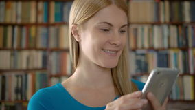 Happy smiling student standing in library using smartphone, browsing, reading news, chatting with friends. Happy smiling woman standing in library. Using her stock video