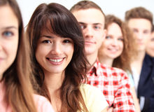 Happy Smiling Students Standing In Row. Young people standing in a row while beautiful young women standing in front of them and smiling Stock Image