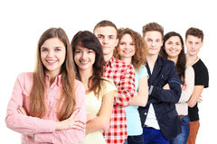 Happy Smiling Students Standing In Row. Young people standing in a row while beautiful young women standing in front of them and smiling Stock Photo