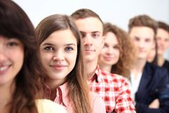 Happy Smiling Students Standing In Row. Young people standing in a row while beautiful young women standing in front of them and smiling Royalty Free Stock Image
