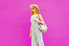 Happy smiling stylish woman walking in summer round straw hat, white striped jumpsuit on colorful pink wall stock photo
