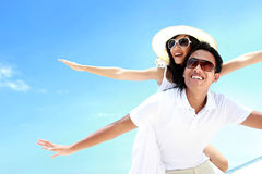 Happy smiling summer couple piggyback together with arms outstre. Tched at beautiful beach Stock Images