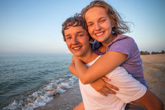 Happy smiling summer couple teen. Boy giving piggyback ride to girlfriend by the sea royalty free stock photos