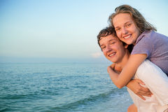 Happy smiling summer couple teen. Boy giving piggyback ride to girlfriend by the sea stock photos