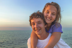 Happy smiling summer couple teen. Boy giving piggyback ride to girlfriend by the sea royalty free stock image