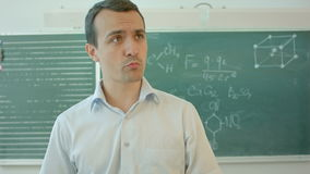 Happy smiling teacher or student man standing near chalkboard, talking on camera. Professional shot on BMCC RAW with high dynamic range. You can use it e.g in stock video footage