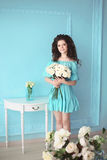 Happy smiling teen brunette with white roses bunch of flowers in. Blue dress posing ba the wall. Curly hairstyle Royalty Free Stock Photography