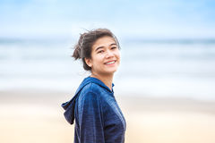 Happy, smiling teen girl in blue hoodie jacket  on beach Stock Images