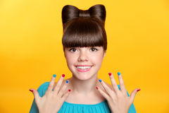 Happy smiling teen girl with bow hairstyle and colourful manicur Royalty Free Stock Photography