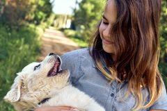 Happy teen girl playing with a cute puppy of a pyrenean mountain dog holding it on her hands in summer day outdoors. Happy smiling teen girl playing with a cute royalty free stock photo