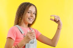 Close up of happy smiling teen girl taking pill with cod liver oil omega-3 and holding a glass of fresh water with yellow backgrou Royalty Free Stock Photo