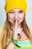 Happy smiling  teen   shows a sign  SILENCE. Happy smiling  hippie with Easter candies on lips  shows a sign  SILENCE Stock Photography