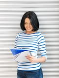 Happy and smiling teenage girl with big notepad Stock Images