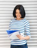 Happy and smiling teenage girl with big notepad Stock Image