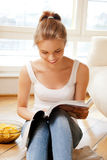 Happy and smiling teenage girl with magazine Royalty Free Stock Image