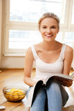 Happy and smiling teenage girl with magazine Royalty Free Stock Photo