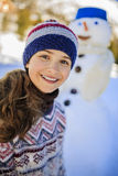 Happy smiling teenage girl playing with a snowman. Royalty Free Stock Image