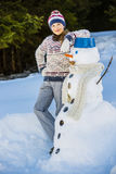 Happy smiling teenage girl playing with a snowman on a snowy win Stock Image