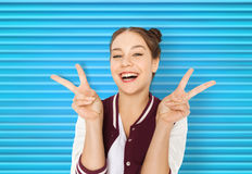 Happy smiling teenage girl showing peace sign. People, gesture and teens concept - happy smiling pretty teenage girl showing peace sign over blue ribbed Stock Photo