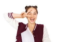 Happy smiling teenage girl showing peace sign. People, gesture and teens concept - happy smiling pretty teenage girl showing peace sign and winking Royalty Free Stock Photo
