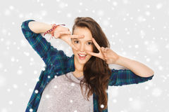 Happy smiling teenage girl showing peace sign. Winter, christmas, people, gesture and teens concept - happy smiling pretty teenage girl showing peace sign over Stock Photo