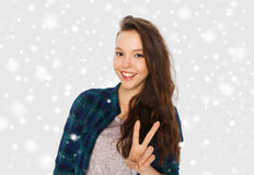 Happy smiling teenage girl showing peace sign. Winter, christmas, people, gesture and teens concept - happy smiling pretty teenage girl showing peace sign over Royalty Free Stock Image