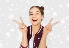 Happy smiling teenage girl showing peace sign Stock Photo
