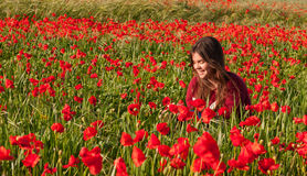 Happy smiling teenage girl sitting in a red poppy field Stock Image