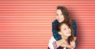 Happy smiling teenage girls or friends hugging stock photos