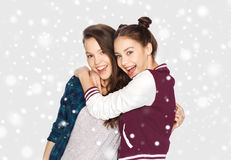 Happy smiling teenage girls hugging over snow Stock Image