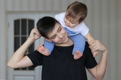 Happy smiling teenager boy holding his little brother sitting on his neck. Family concept Royalty Free Stock Image