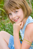 Happy smiling teenager girl on the green meadow Royalty Free Stock Images