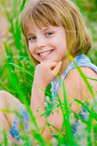 Happy smiling teenager girl on the green meadow Royalty Free Stock Image