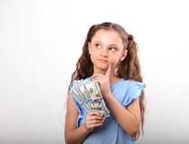 Happy smiling thinking rich kid girl holding money the hand and. Looking up on white background with empty copy space Stock Photography