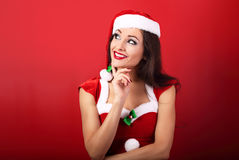 Happy smiling thinking woman in santa claus christmas costume lo Royalty Free Stock Images