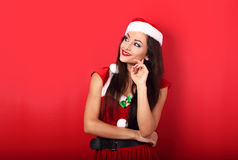 Happy smiling thinking woman in santa claus christmas costume lo Stock Image