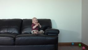 Happy smiling toddler boy watching tv with remote control in hands stock video