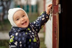Happy smiling toddler in white woolen hat opening old door to somewhere. Children safety concept royalty free stock photos