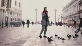 Happy smiling tourist girl takes smartphone photos of pigeons flock standing on city square in Venice, Italy slow motion. Birds fly around excited woman at stock footage